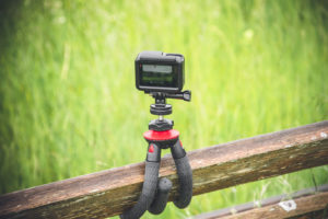 Detailaufnahme einer Action Kamera die an einem Holzzaun befestigt ist