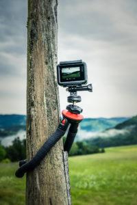 Detailaufnahme einer Action Kamera die an einem Holzpfahl befestigt ist