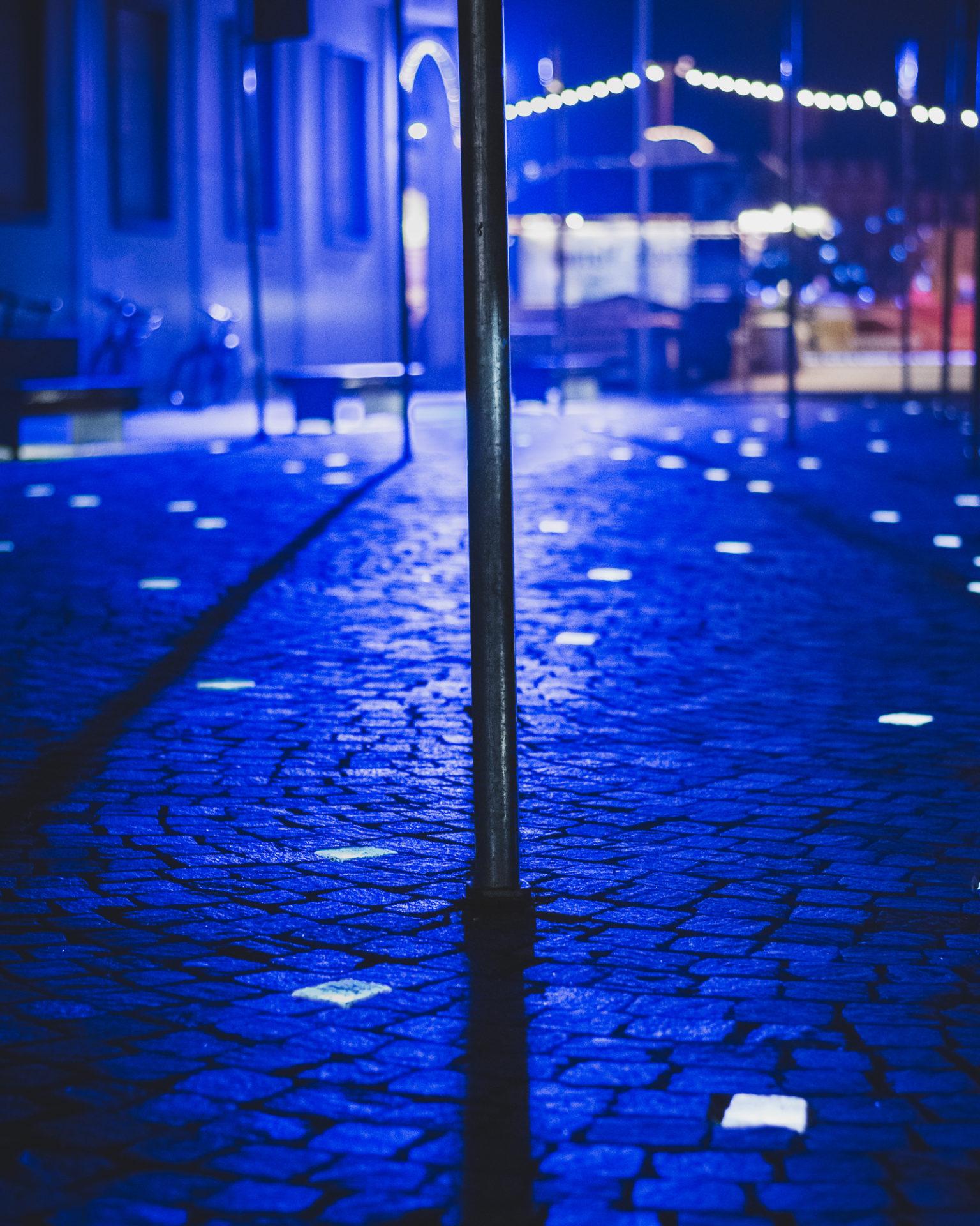 Aufnahme von blauen Lichtern, Stangen und Kopfsteinpflaster mit teils beleuchteten Steinen