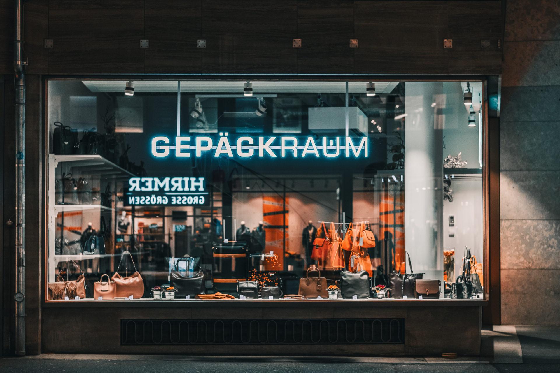 Ansicht eines Schaufensters mit Leuchtreklame und Spiegelungen in der Scheibe