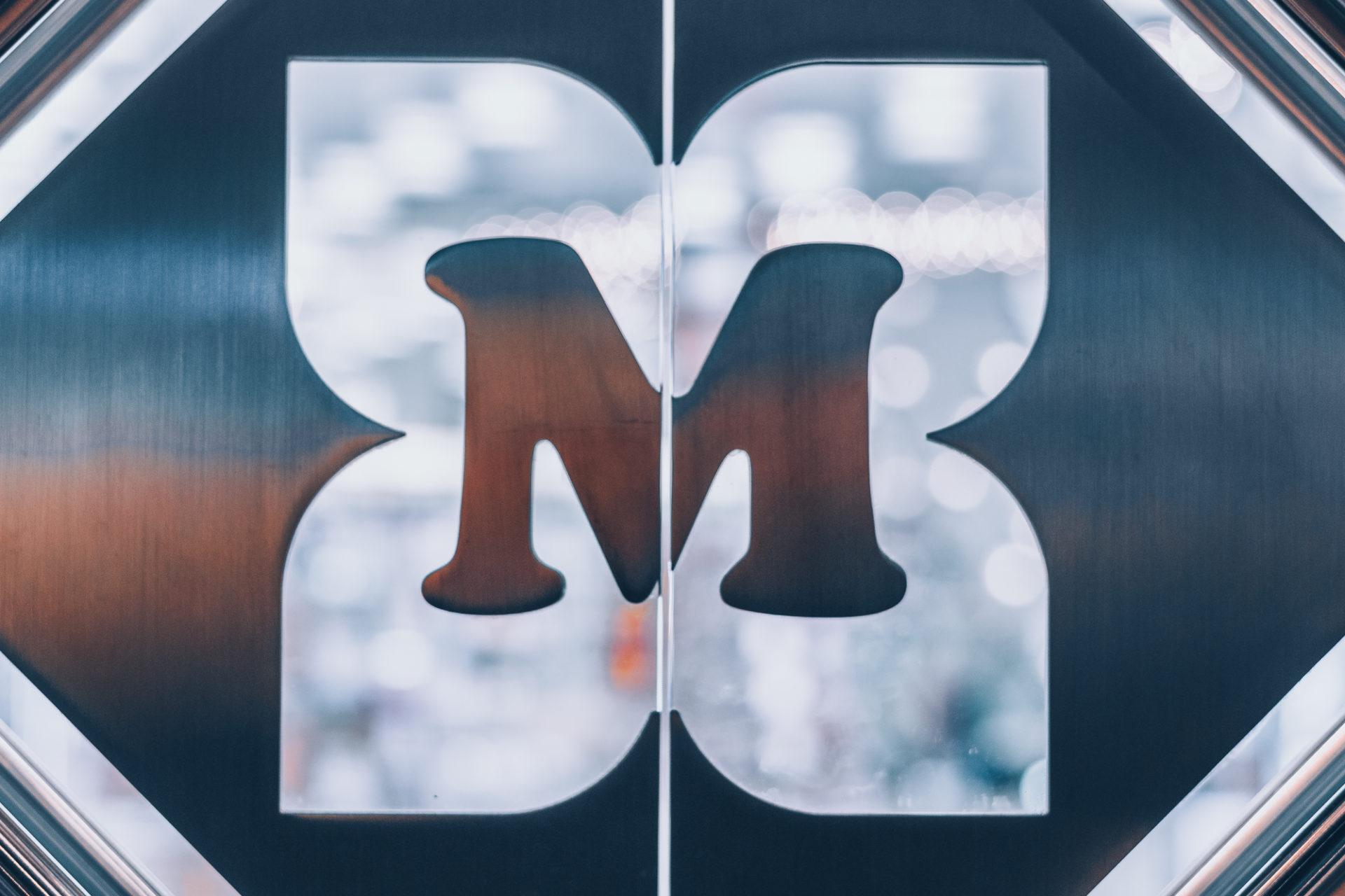 Nahaufnahme eines stilisierten Logos mit dem Buchstaben M an der Eingangstür eines Ladenlokals