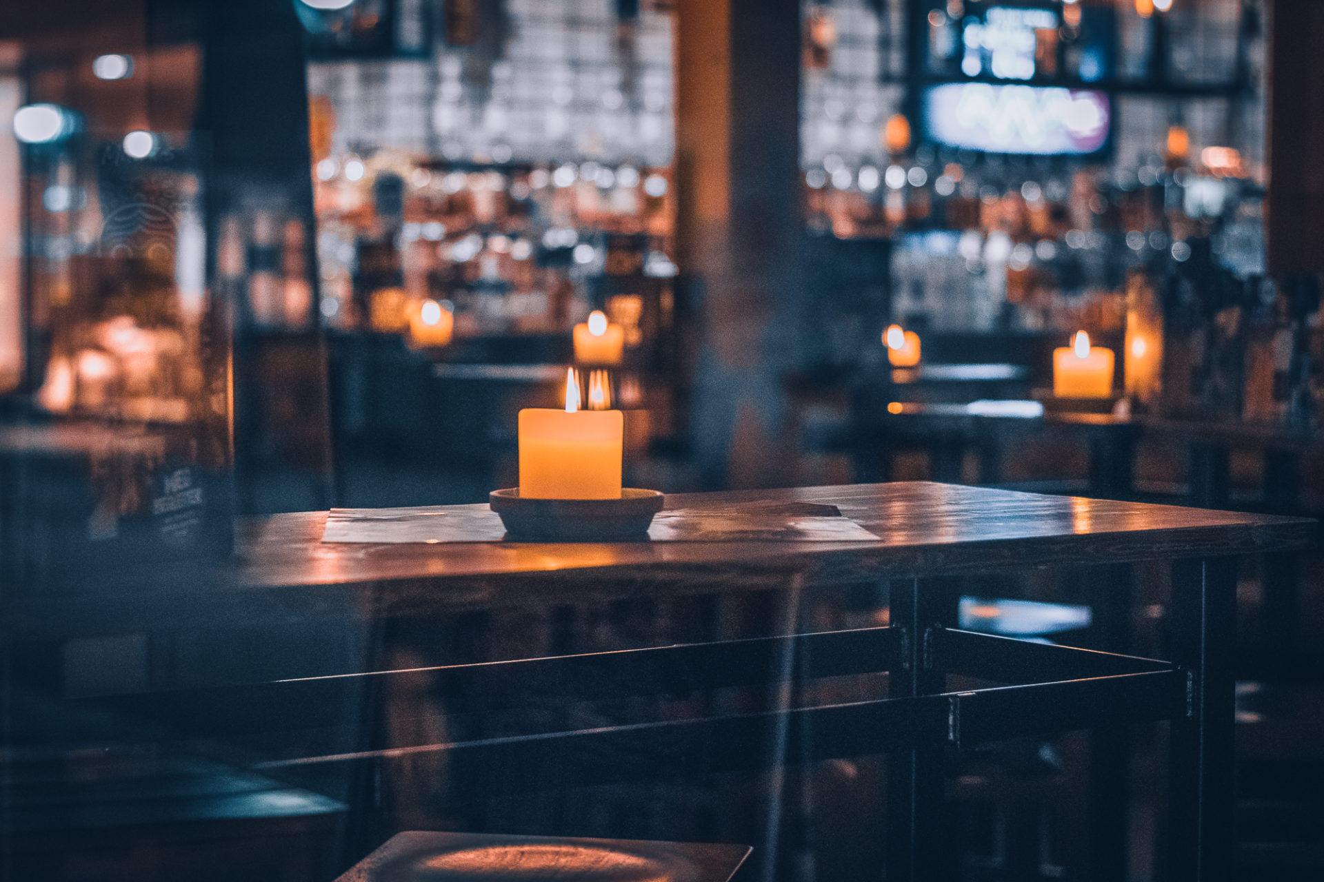 Innenansicht eines Restaurants mit leeren Tischen und Kerzenlicht