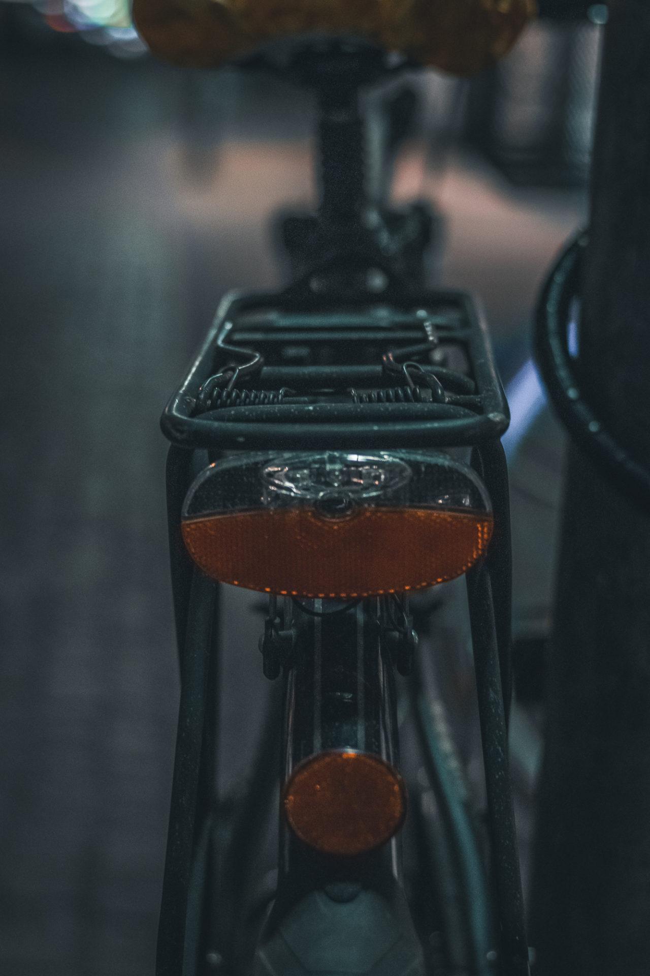 Dunkle Aufnahme von einem Gepäckträger eines Fahrrads mit Rücklichtern und Rückstrahler