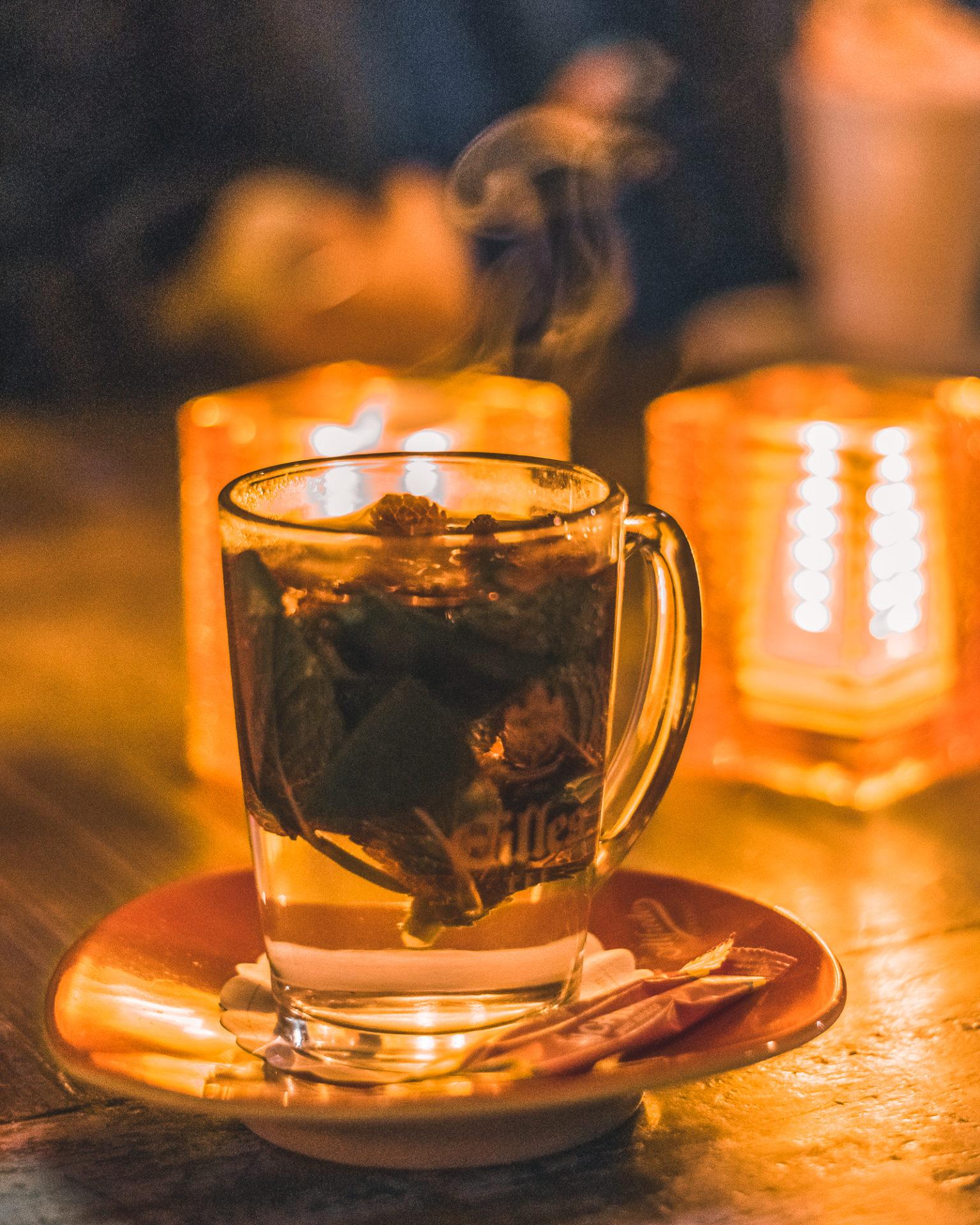 Nahaufnahme eines Glases mit dampfendem Tee im Kerzenlicht