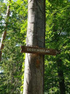 Wegweiser mit der Richtung zum Gedichtpfad an einem Baumstamm
